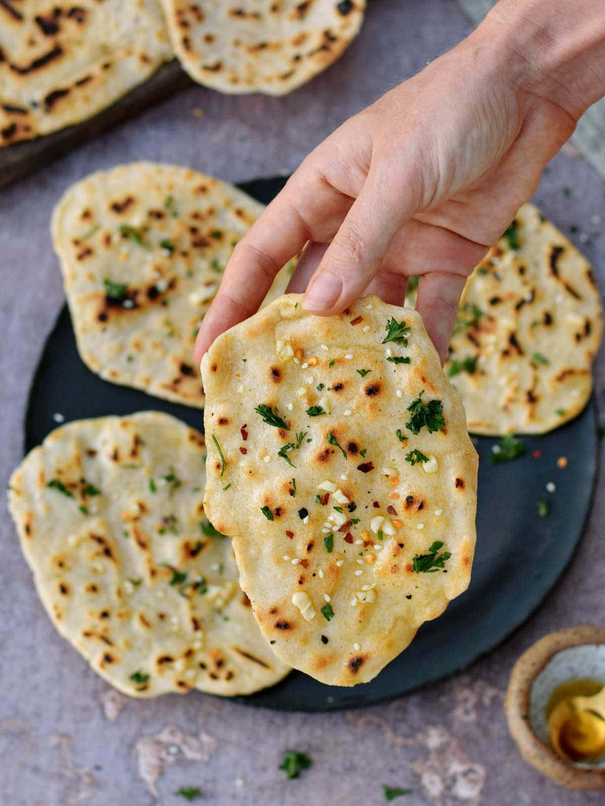 hand holding one of four Indian flatbreads