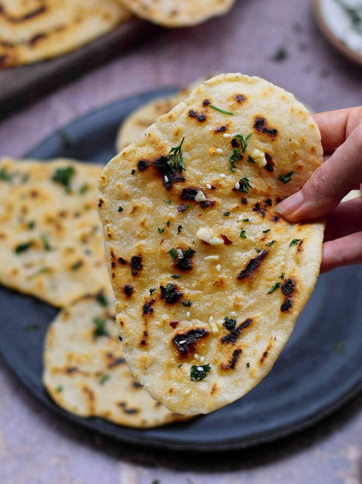 hand holding one vegan gluten-free homemade flatbread with garlic