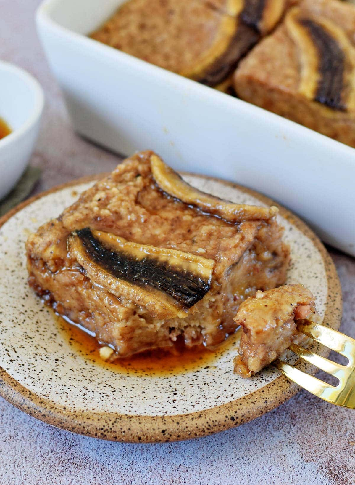 slice of baked oatmeal with caramelized banana on small plate with fork