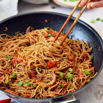 spicy Sriracha noodles in black skillet with chopsticks