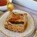 spoon drizzles maple syrup on a vegan baked oatmeal piece with banana on small plate