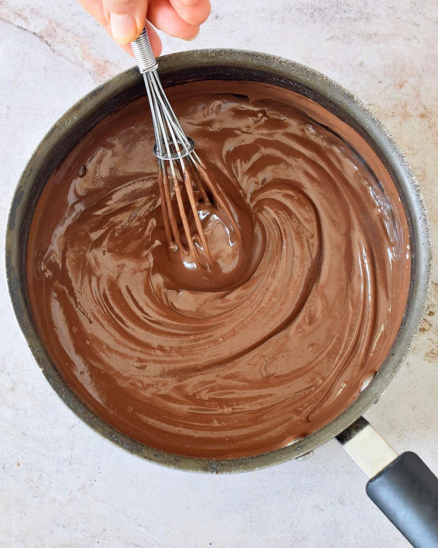 stirring healthy choc pud in black pot