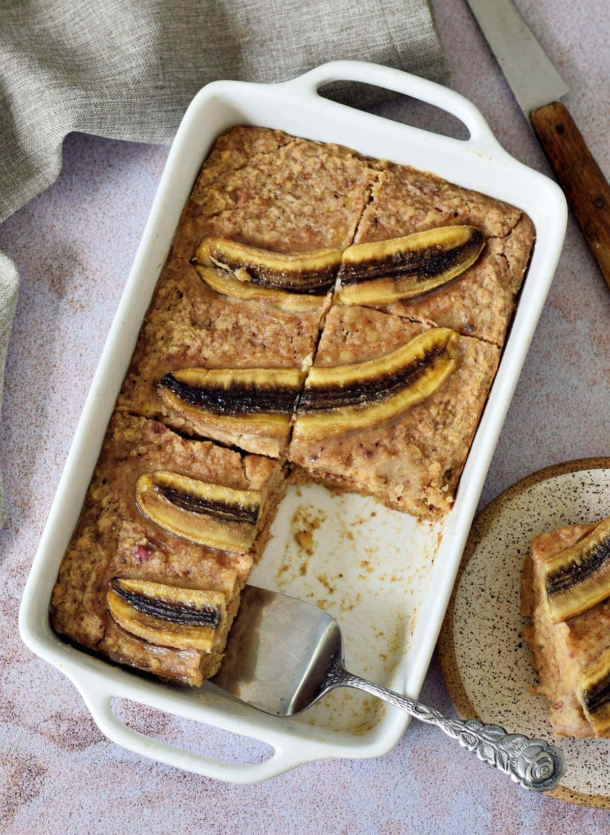 vegan baked oatmeal with banana slices in white pan with piece cut out