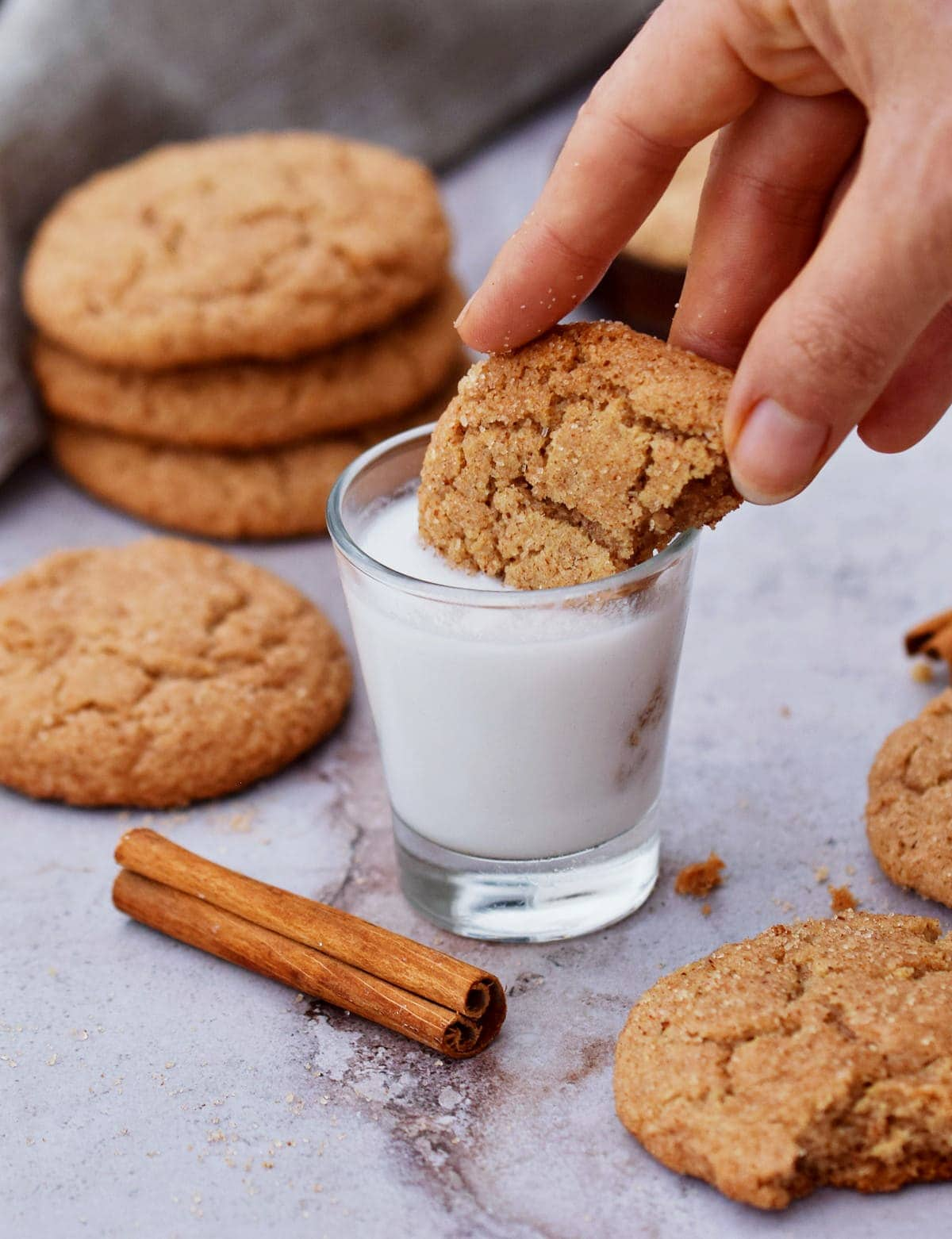 a vegan snickerdoodle cookie dipped in a glass of coconut milk