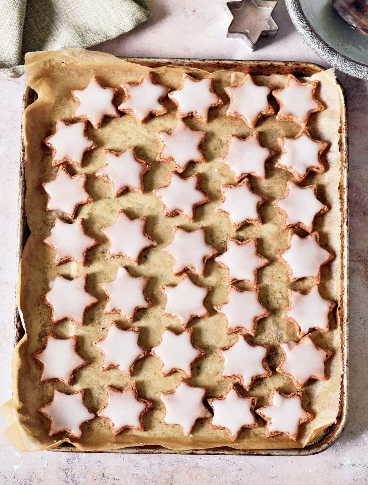 Kekse (vegan) in Sternenform mit Zuckerglasur auf Backblech