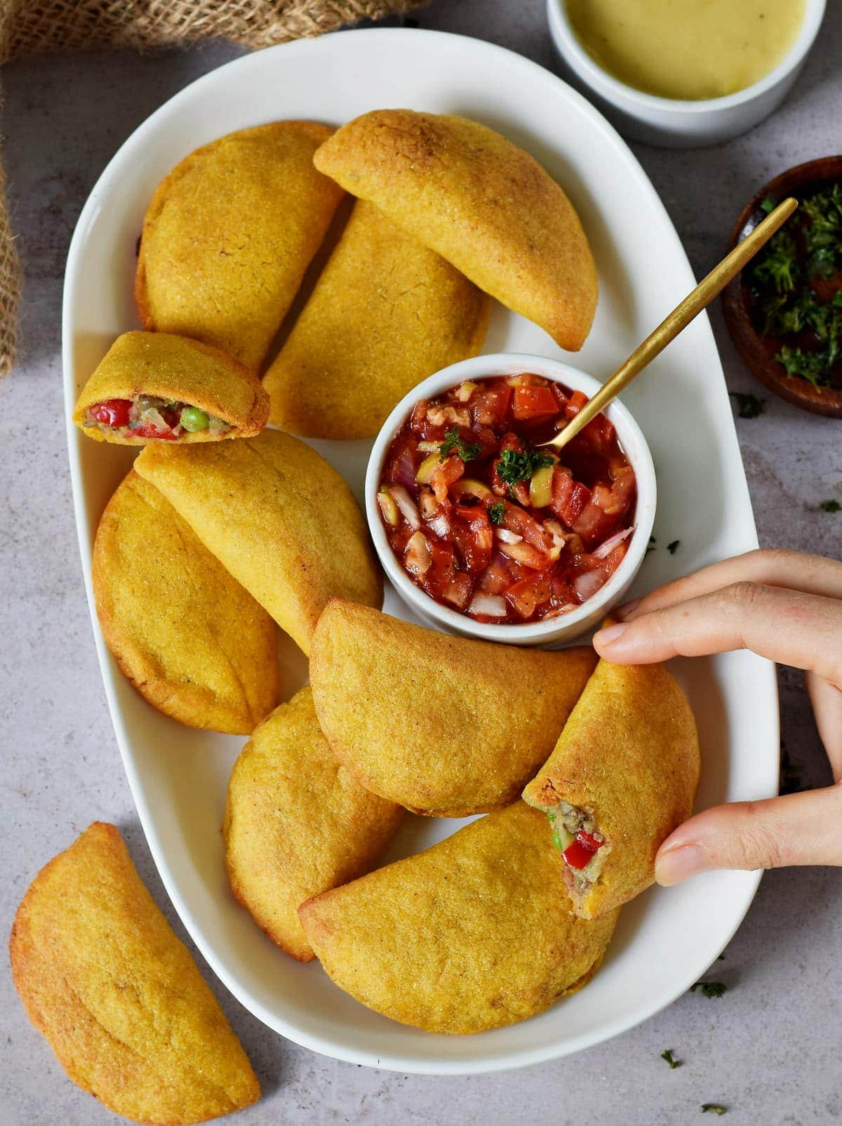 hand grabbing Colombian empanada with veggie filling