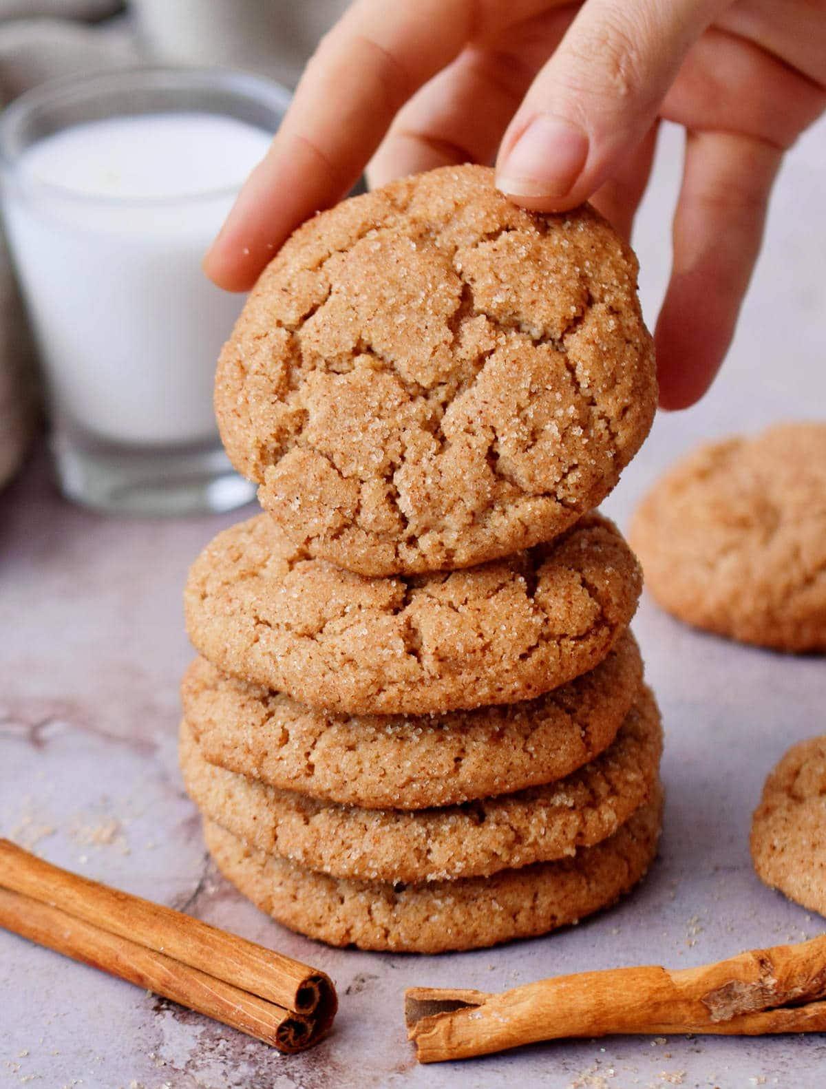 hand grabbing gluten-free vegan snickerdoodles