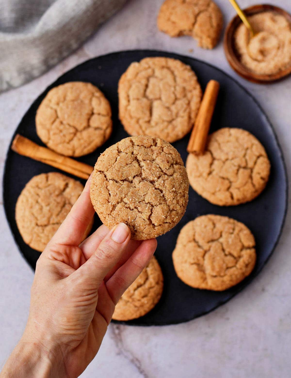 hand holding a vegan snickerdoodle cookie over a black plate