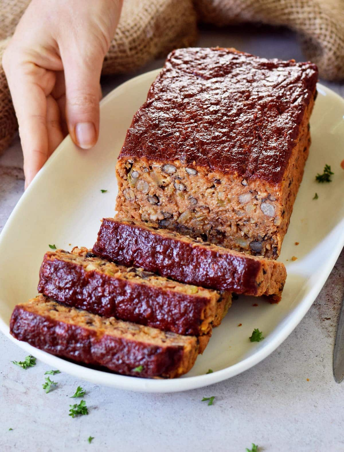 hand holding plate with veggie meatloaf