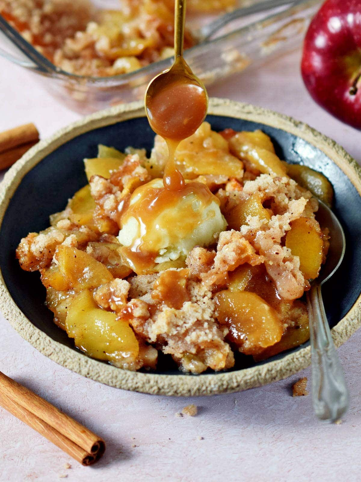 Löffel träufelt Karamellsoße über Apple Crumbe (mit veganem Vanilleeis) auf Teller