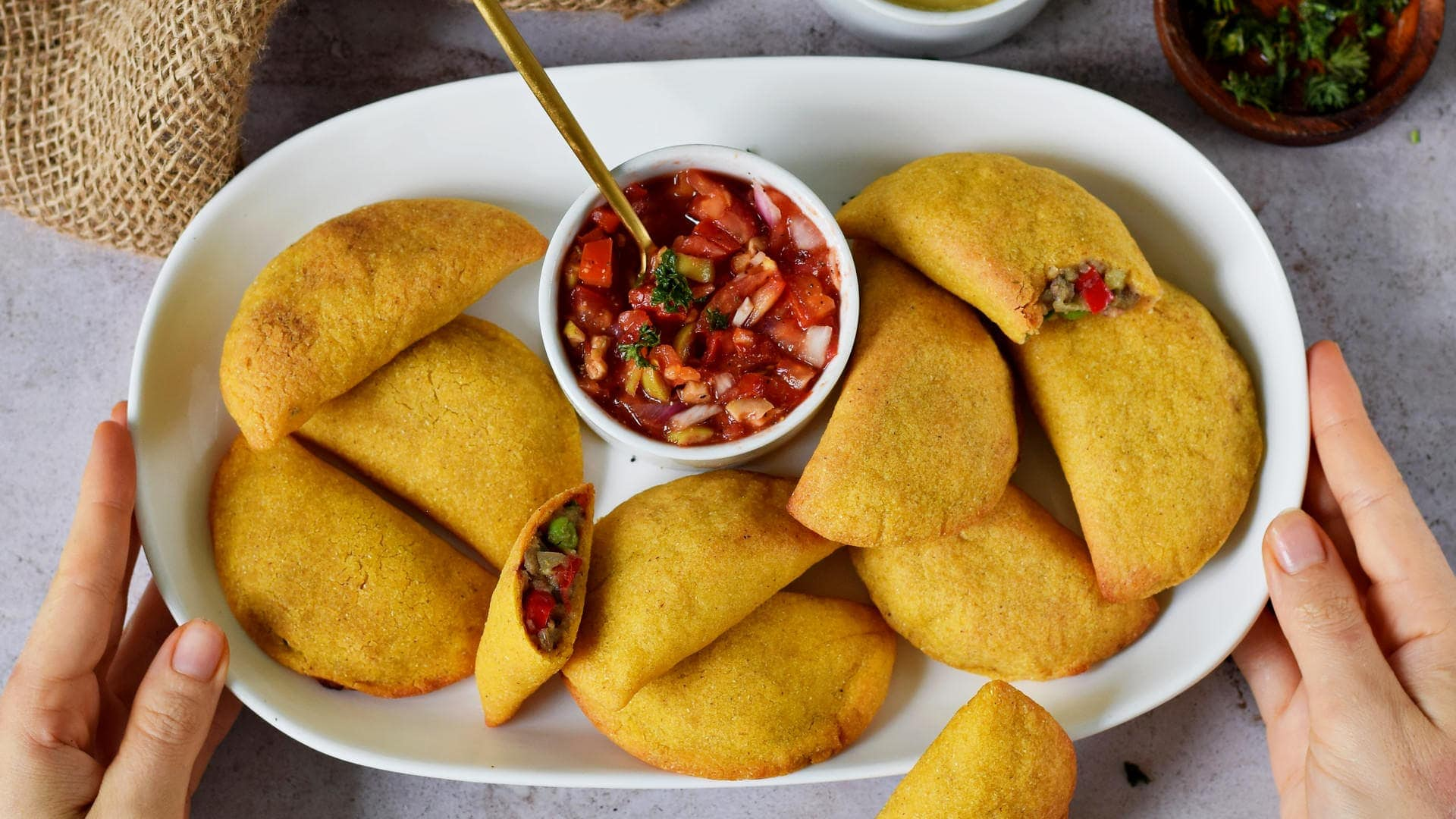 hands holding white plate with vegan empanadas and tomato salsa