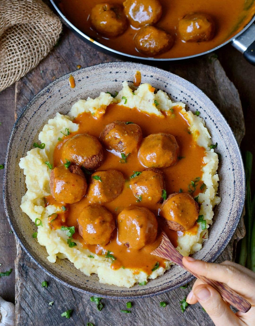 Eating gluten-free vegan meatballs with gravy and mash