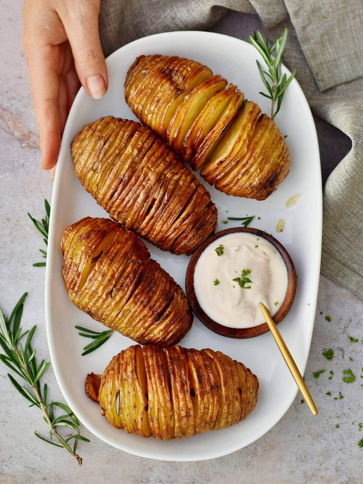 Hand holding a plate with crispy Hasselback potatoes and dip