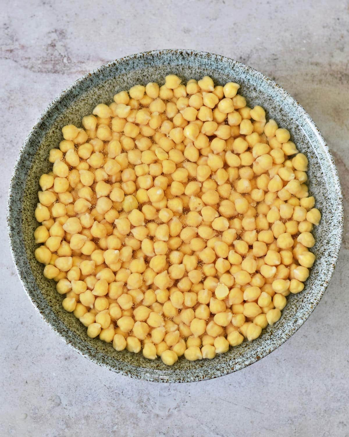 dried chickpeas in bowl soaking in water