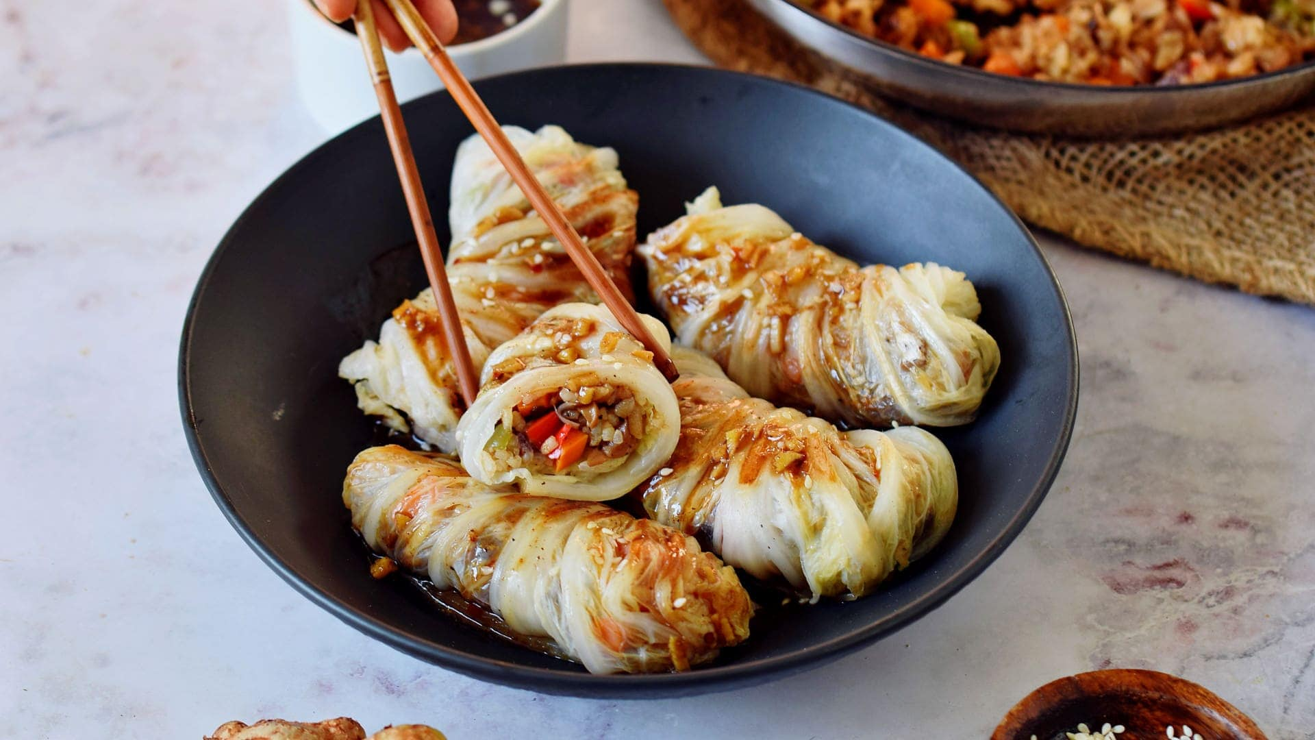 eating cabbage rolls with chopsticks in black bowl