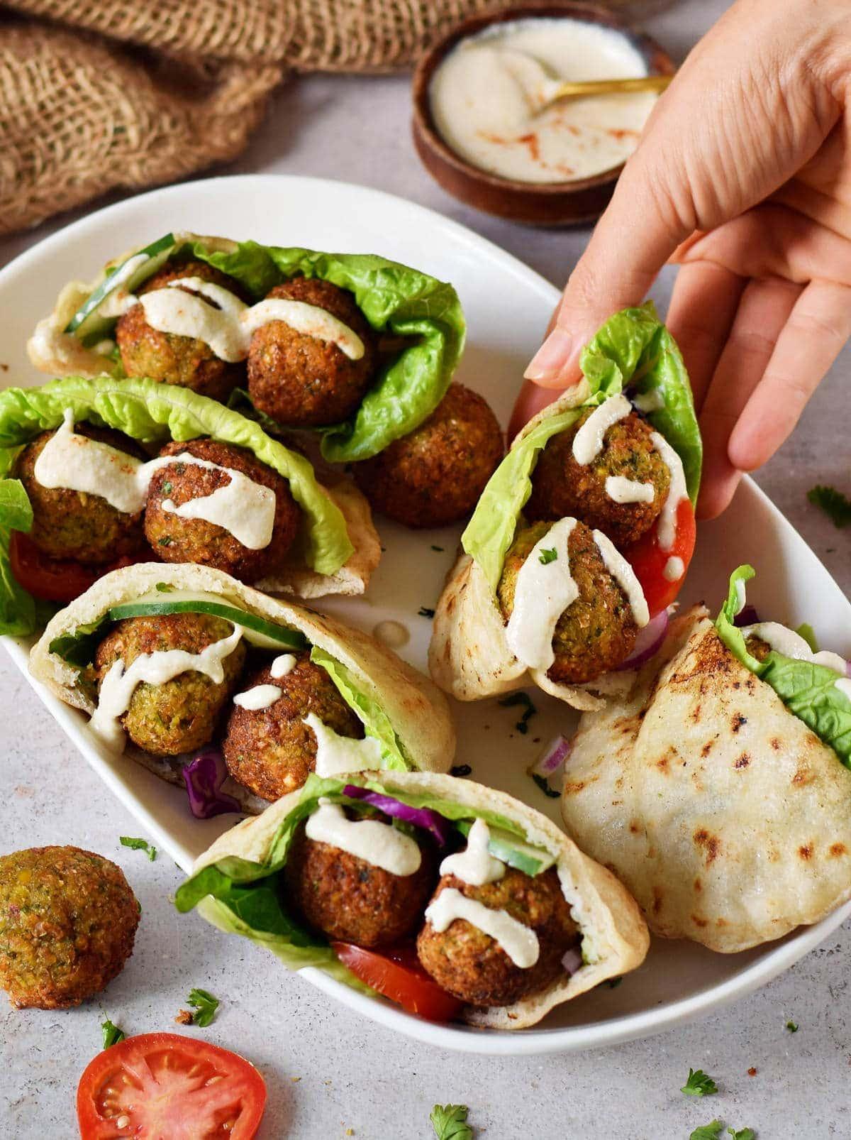 hand grabbing gluten-free pita stuffed with falafel