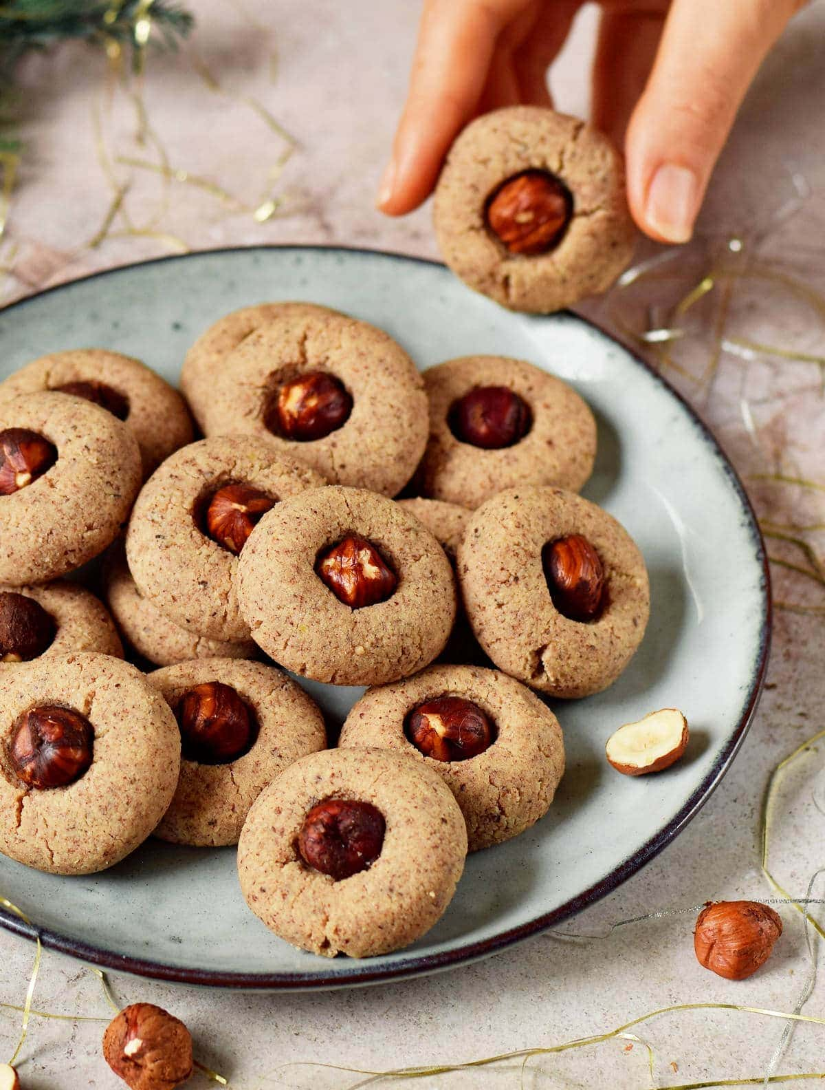hand holding a vegan thumbprint cookie with hazelnuts