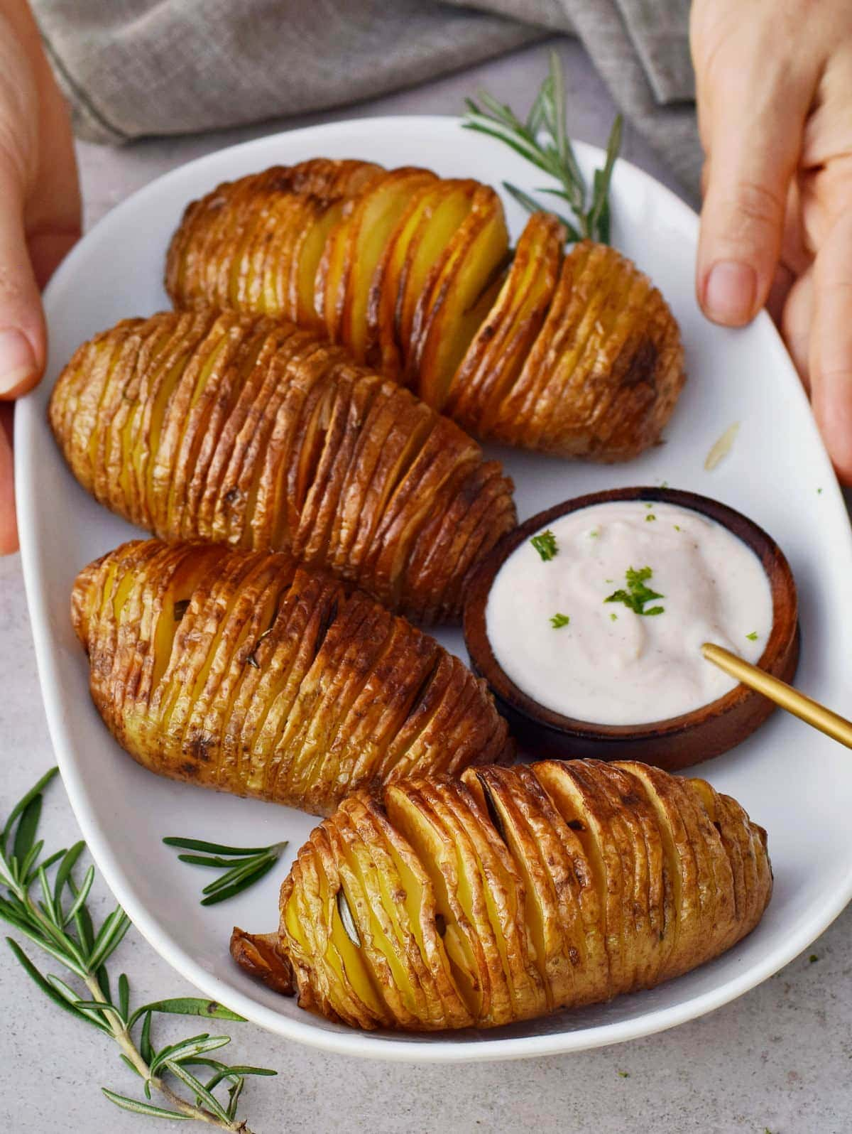 the best Hasselback potatoes with dip on white plate