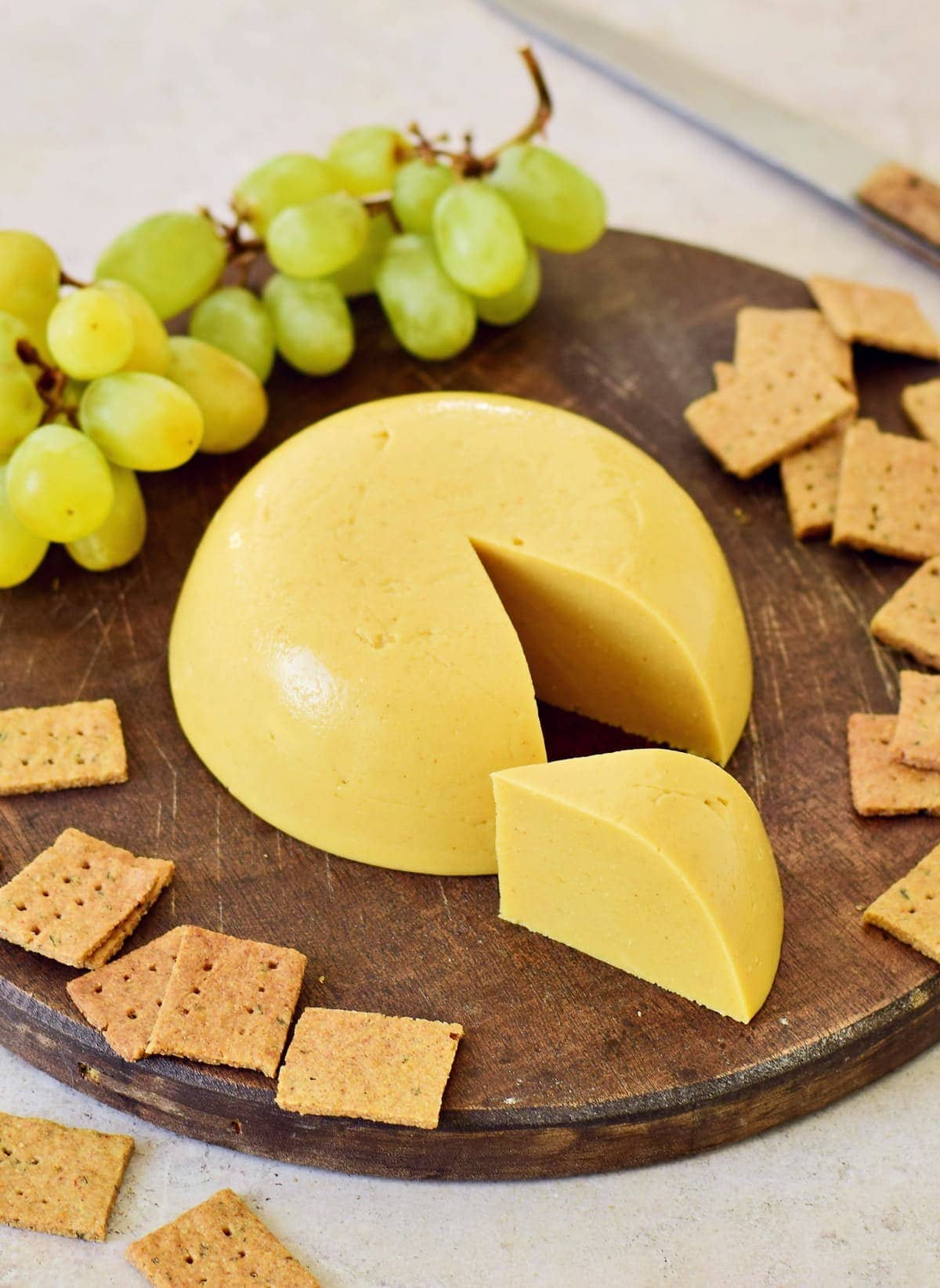 dairy-free cheese on wooden board with a piece cut out