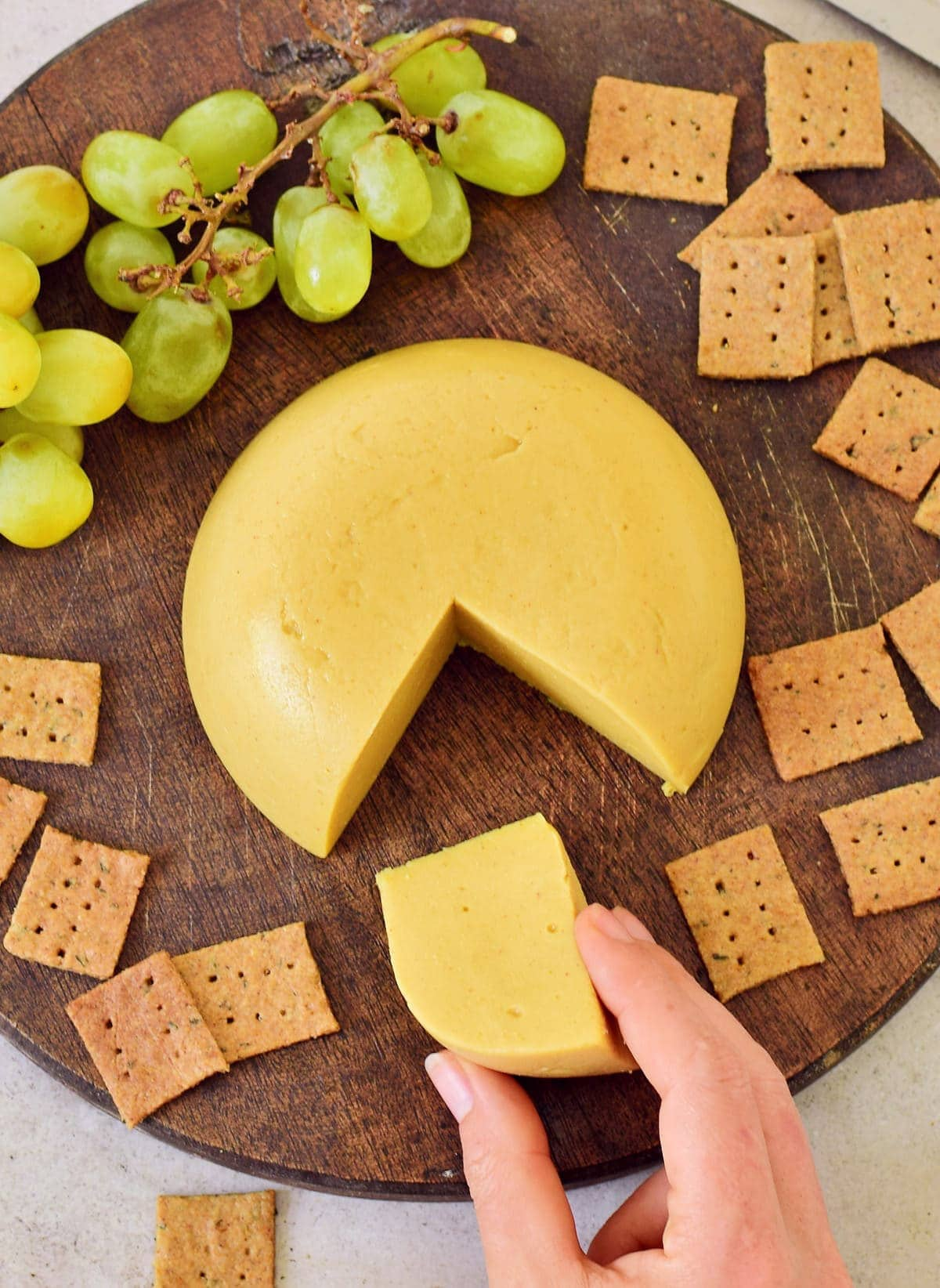 hand grabbing a piece of vegan cheese