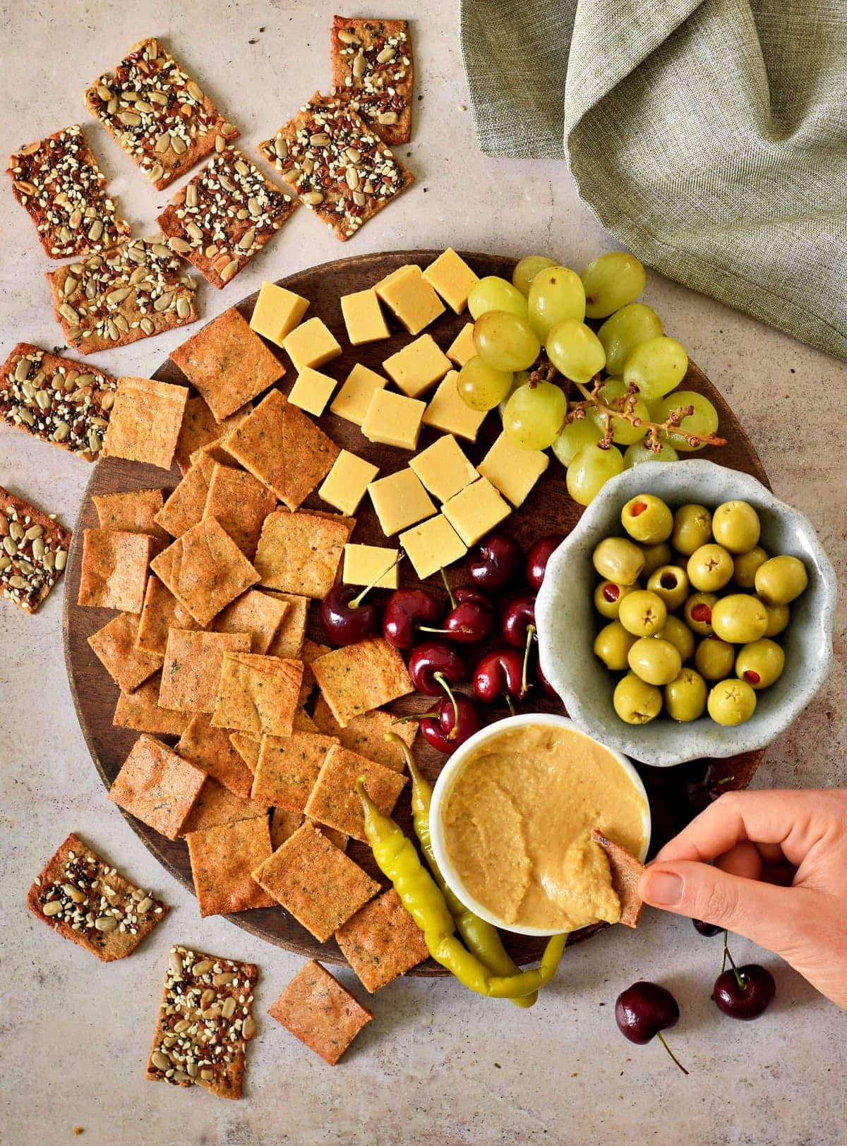 hand holding a vegan cracker in dip on cheese board