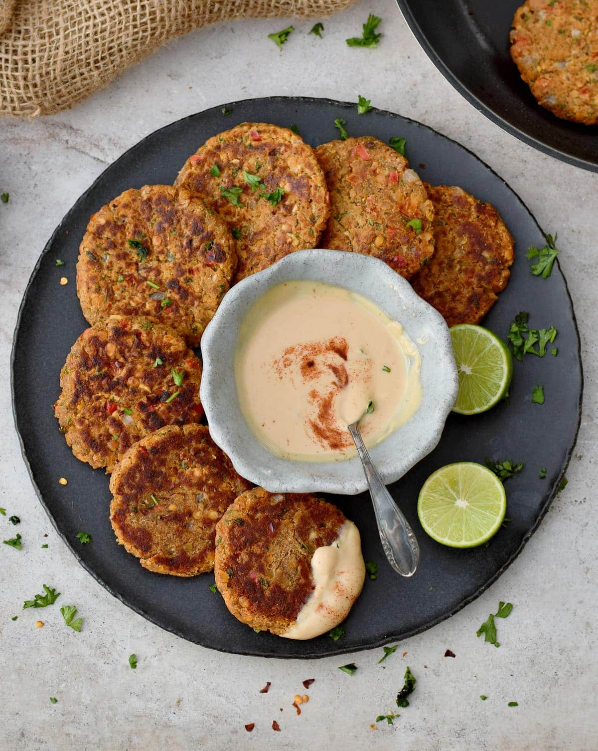 7 red lentil patties with creamy dip and lime on black plate from above