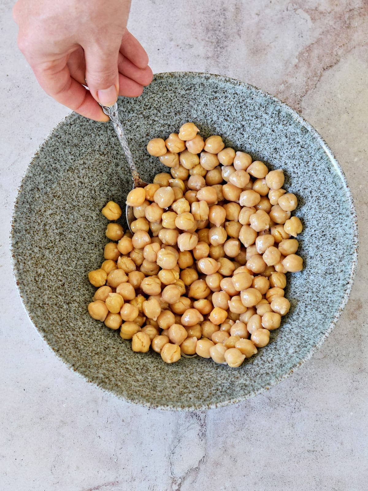 garbanzo beans with oil in bowl with spoon