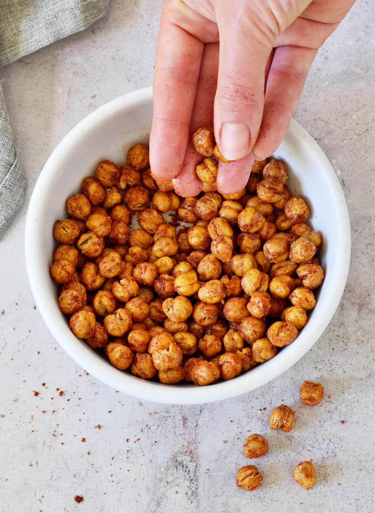 hand grabbing crispy roasted garbanzo beans from white bowl