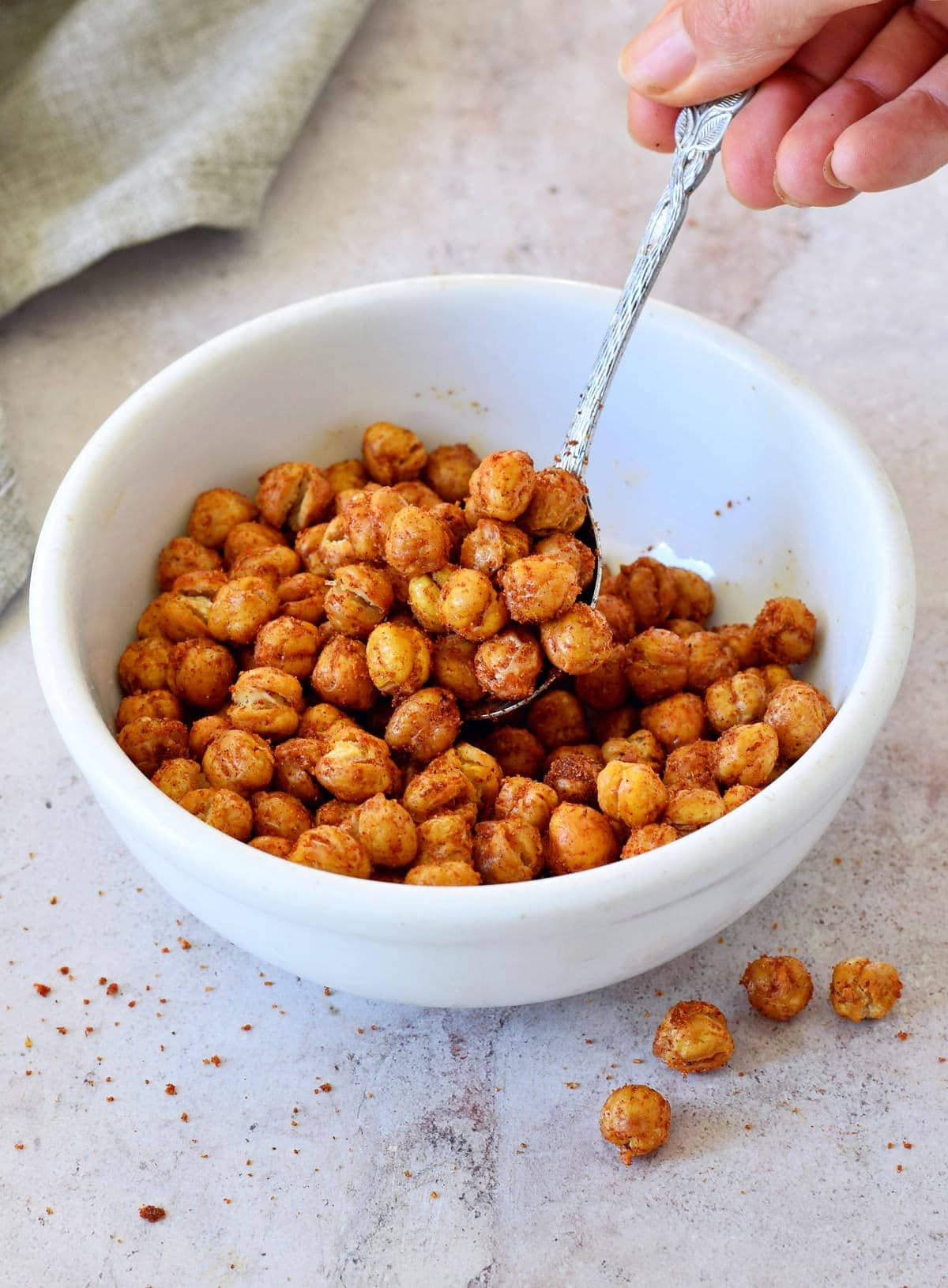 roasted chickpeas in white bowl with spoon in hand