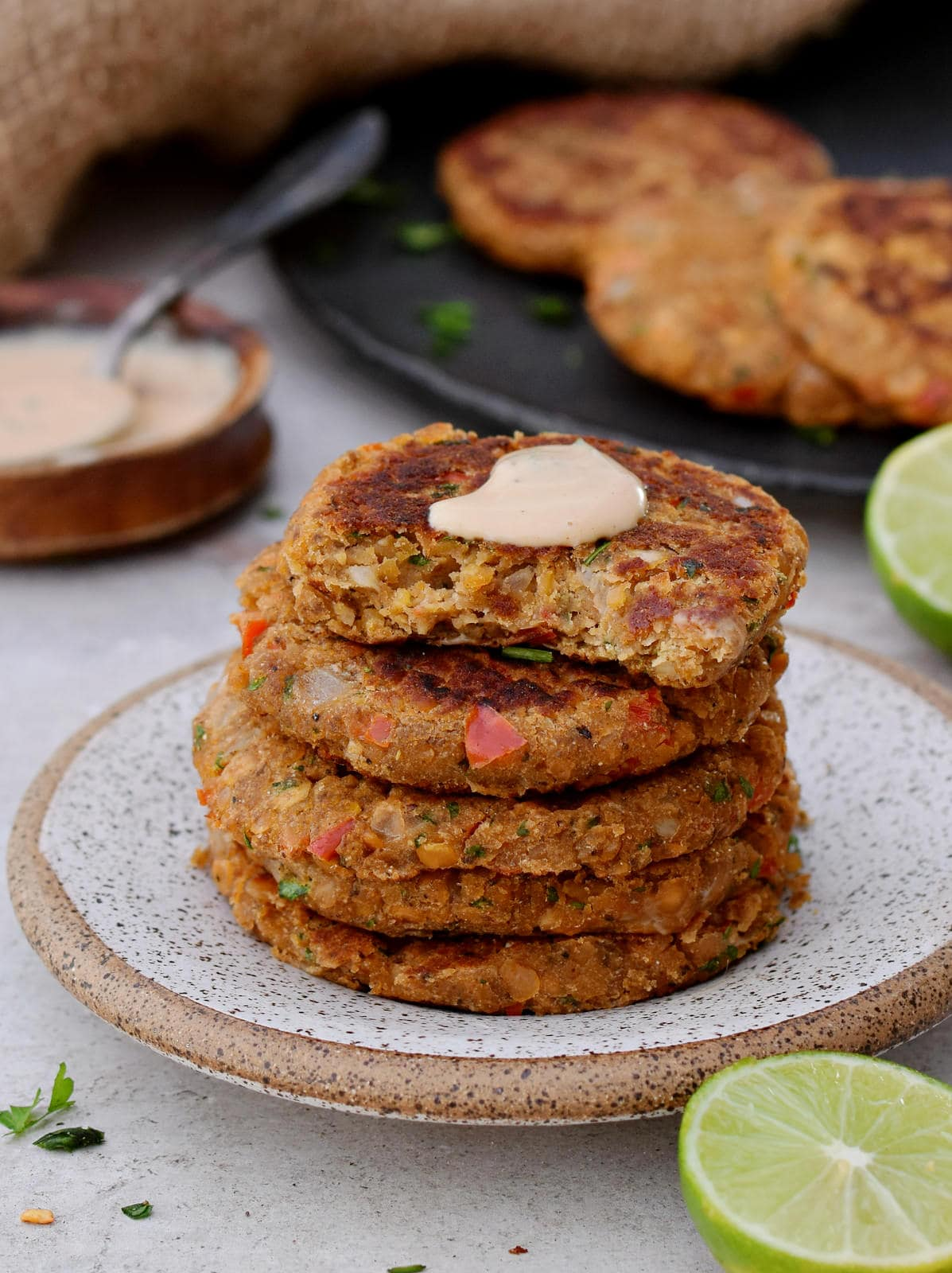 stack of lentil patties with creamy white sauce on top
