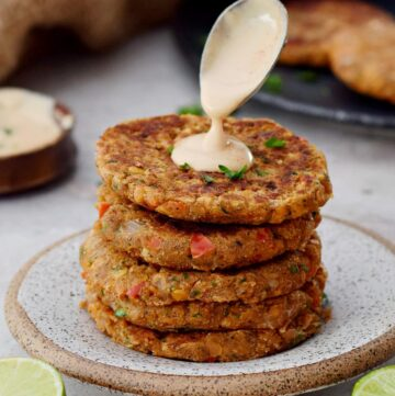 stack of lentil patties with spoon drizzling creamy white sauce on top