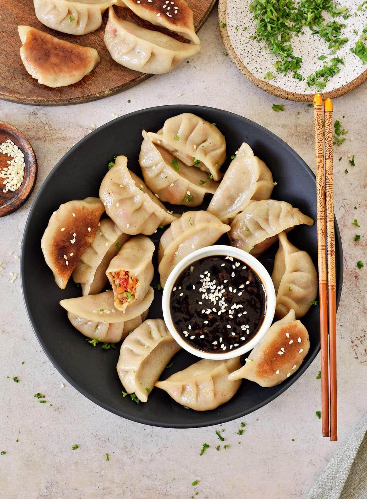vegan dumplings on black plate with Chinese garlic sauce