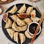 vegan vegetable dumplings on black plate with sauce