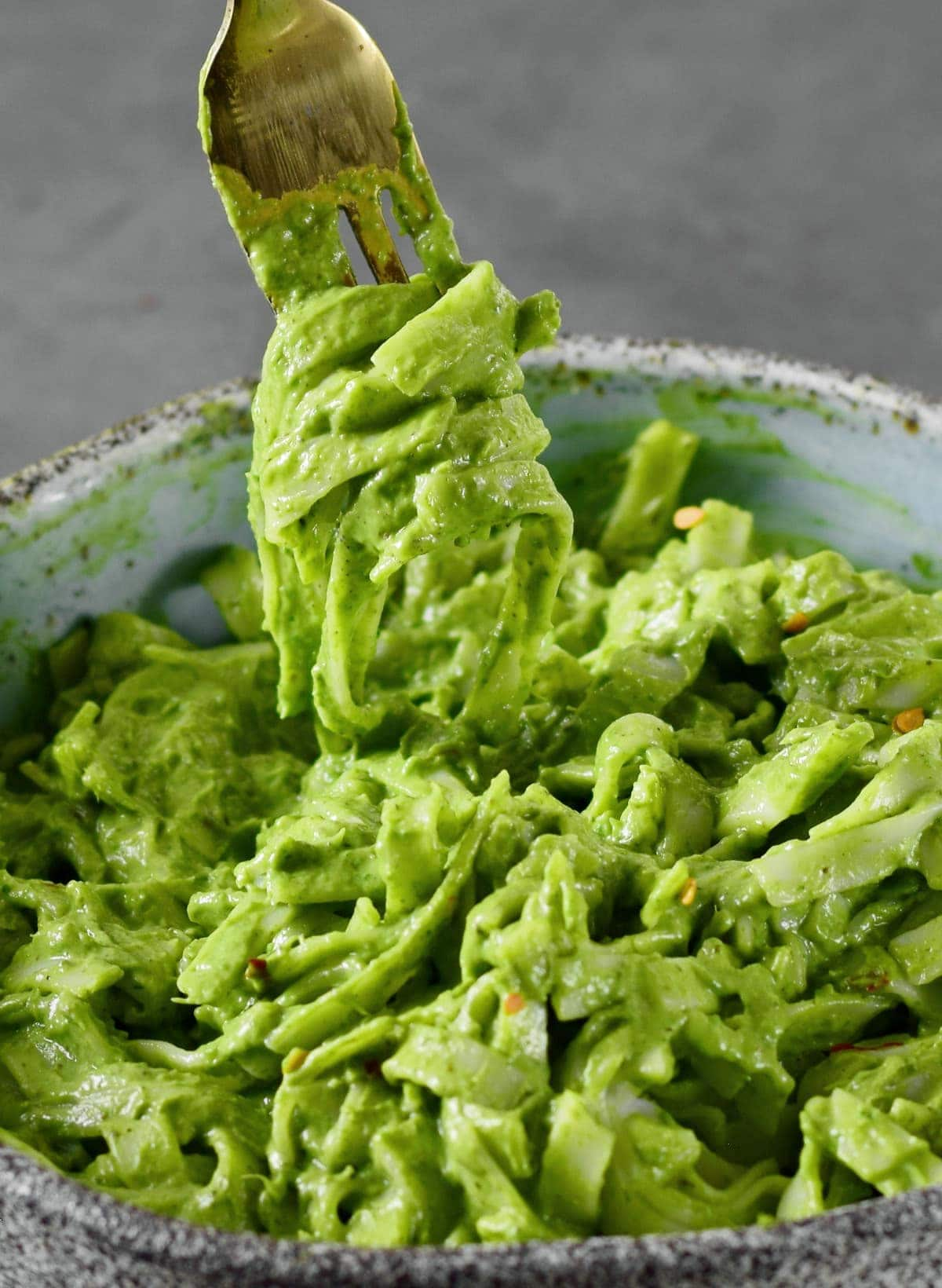 close-up of creamy green noodles in bowl with fork