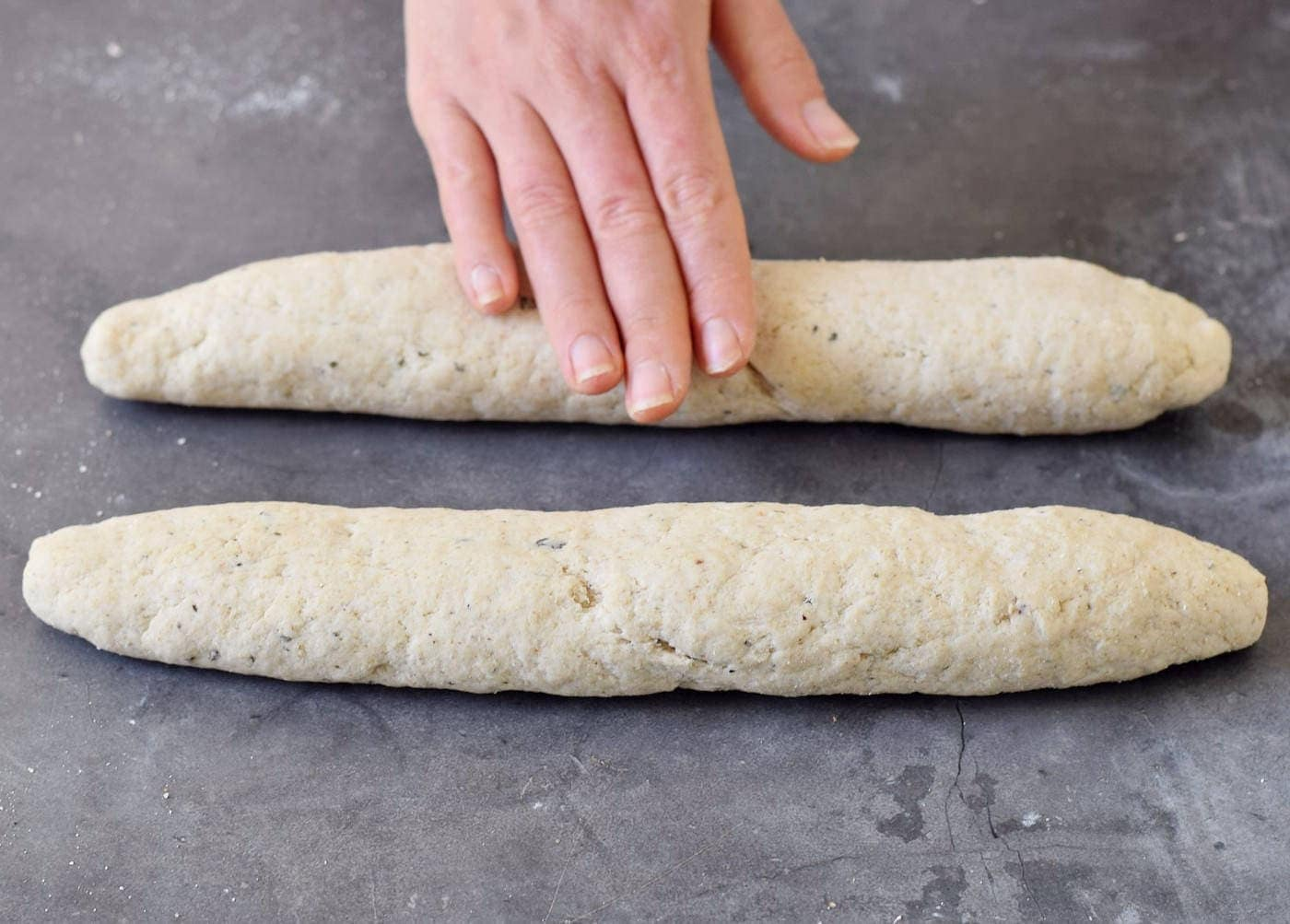 hand rolling out one of two loaves of homemade baguette dough