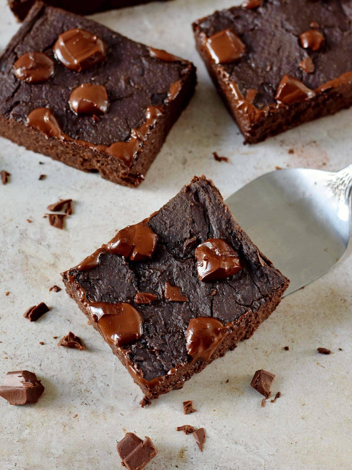 Draufsicht auf 3 vegane schwarze Bohnen-Brownies mit geschmolzener Schokolade obenauf
