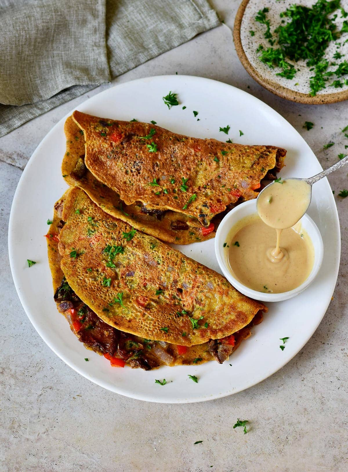 2 vegan omelette on white plate with creamy dressing
