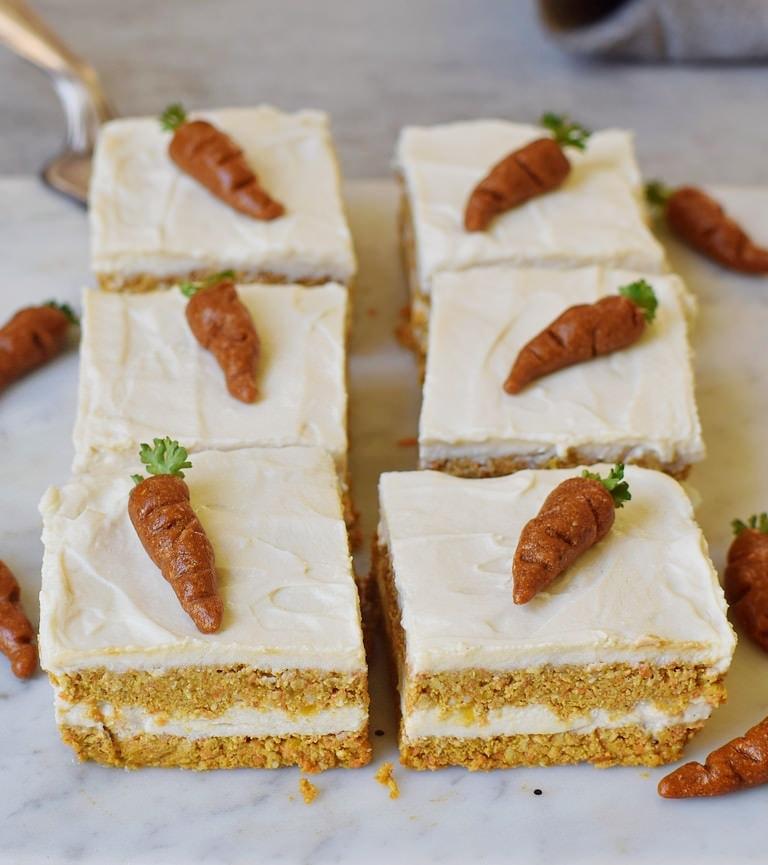 6 eckige Stücke veganer Möhrenkuchen von oben mit weißer Creme und Marzipan-Karotten obendrauf