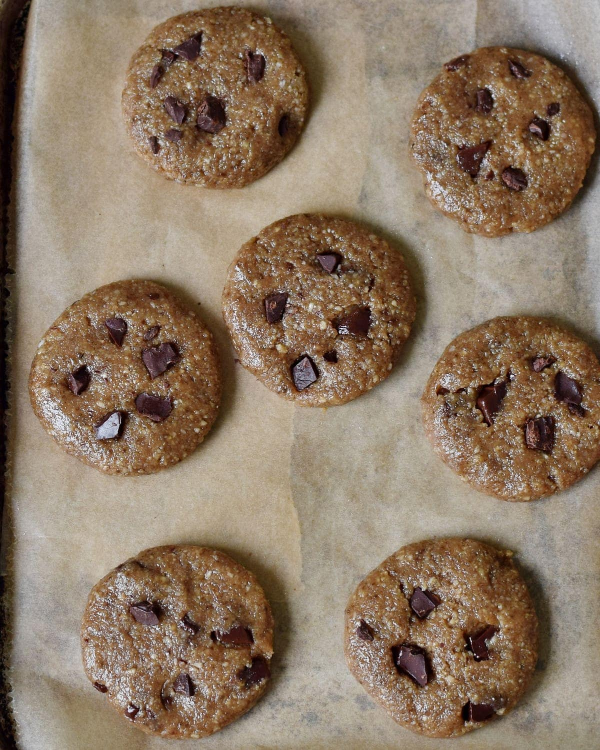 7 cookies with chopped chocolate on parchment paper lined tray