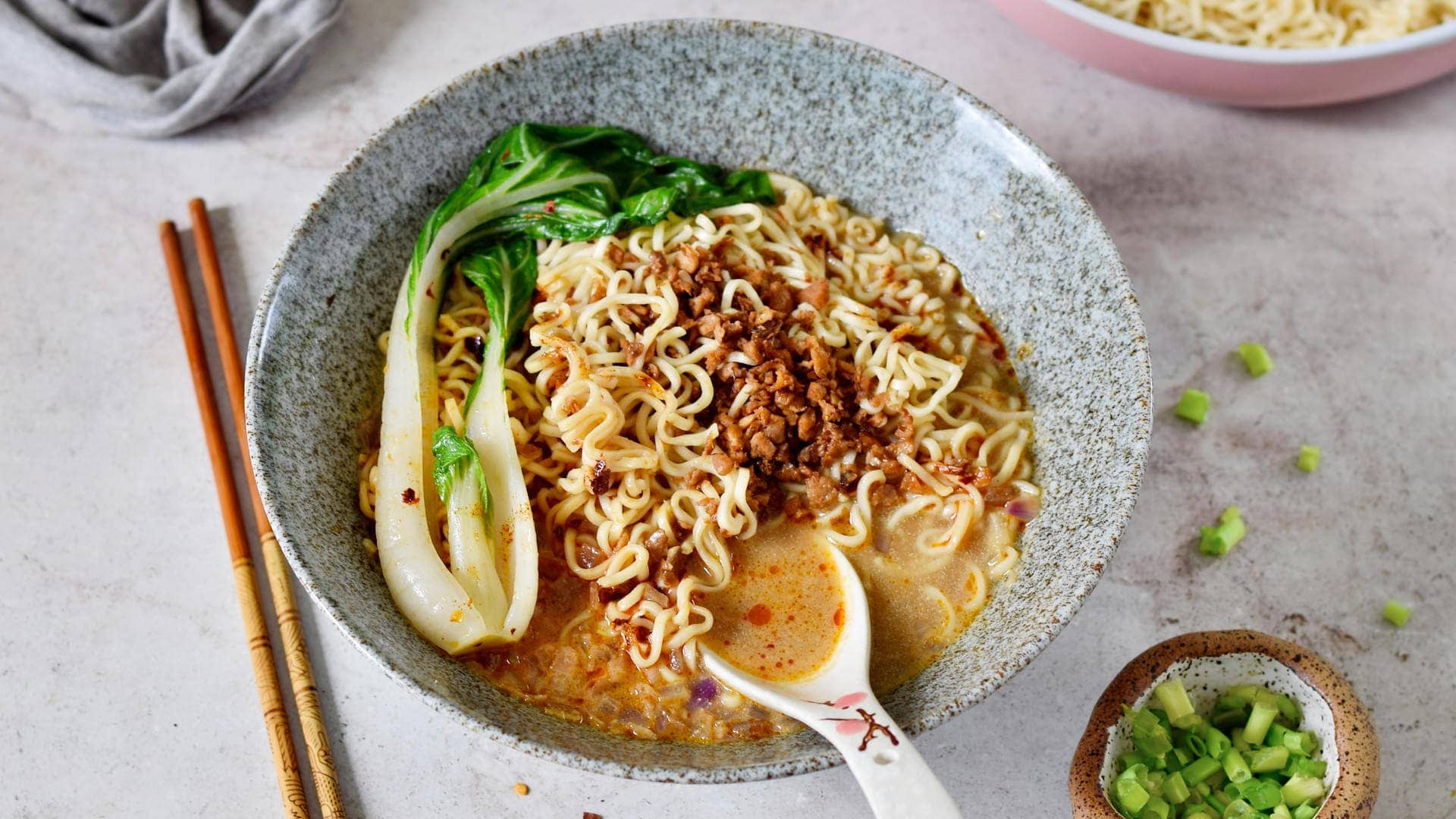 Queraufnahme von Tan Tan Ramen mit Pak Choi in Schüssel mit Löffel