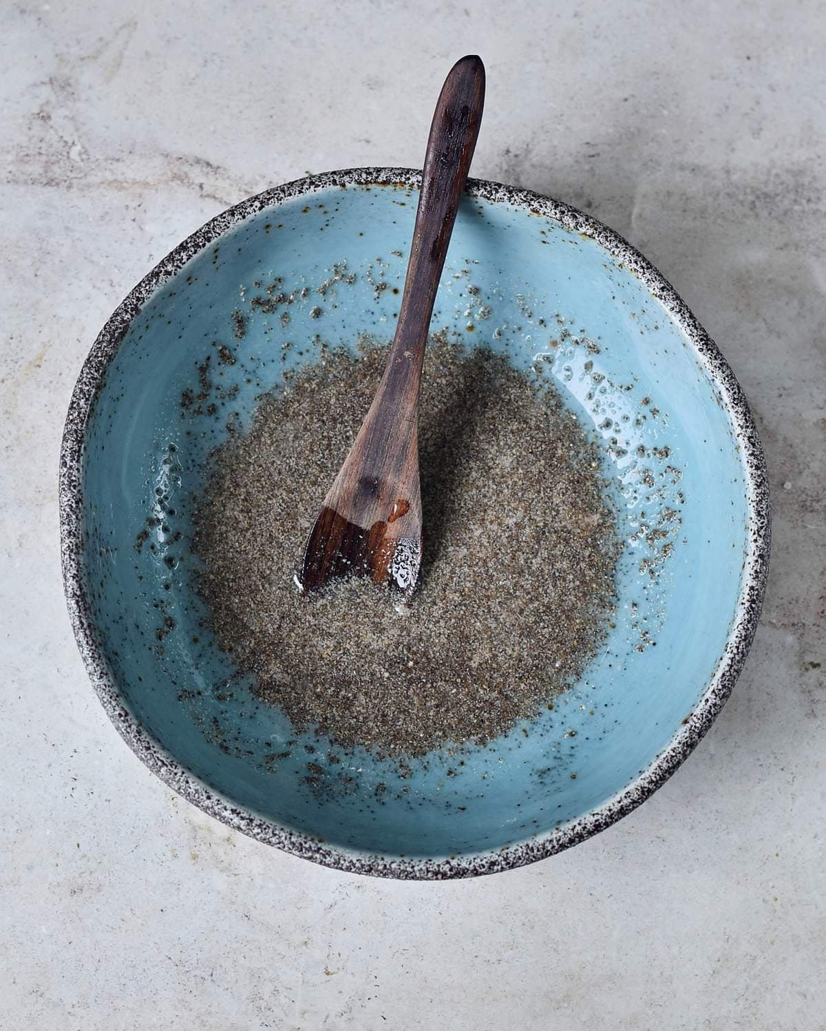 chia eggs in blue bowl with wooden spoon