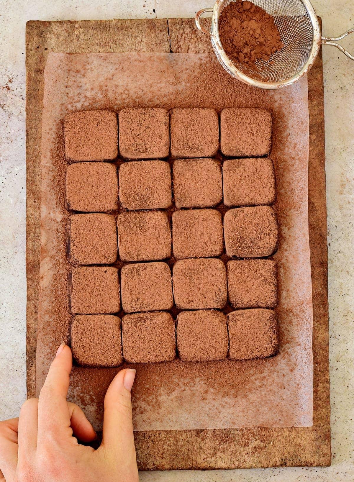 Hand, die nach einem Schokoladentrüffel greift