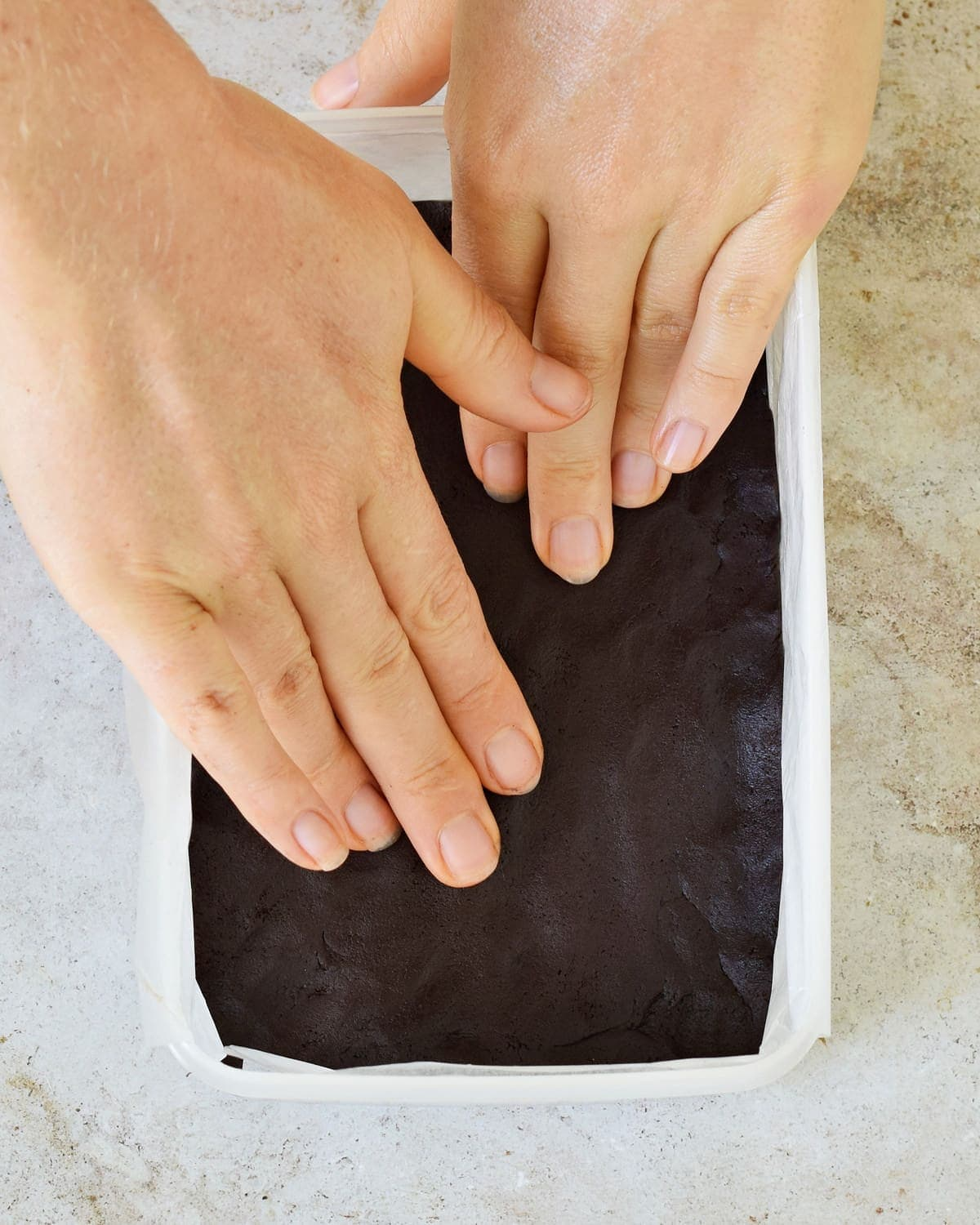 hands spreading chocolate dough in rectangular plastic mold
