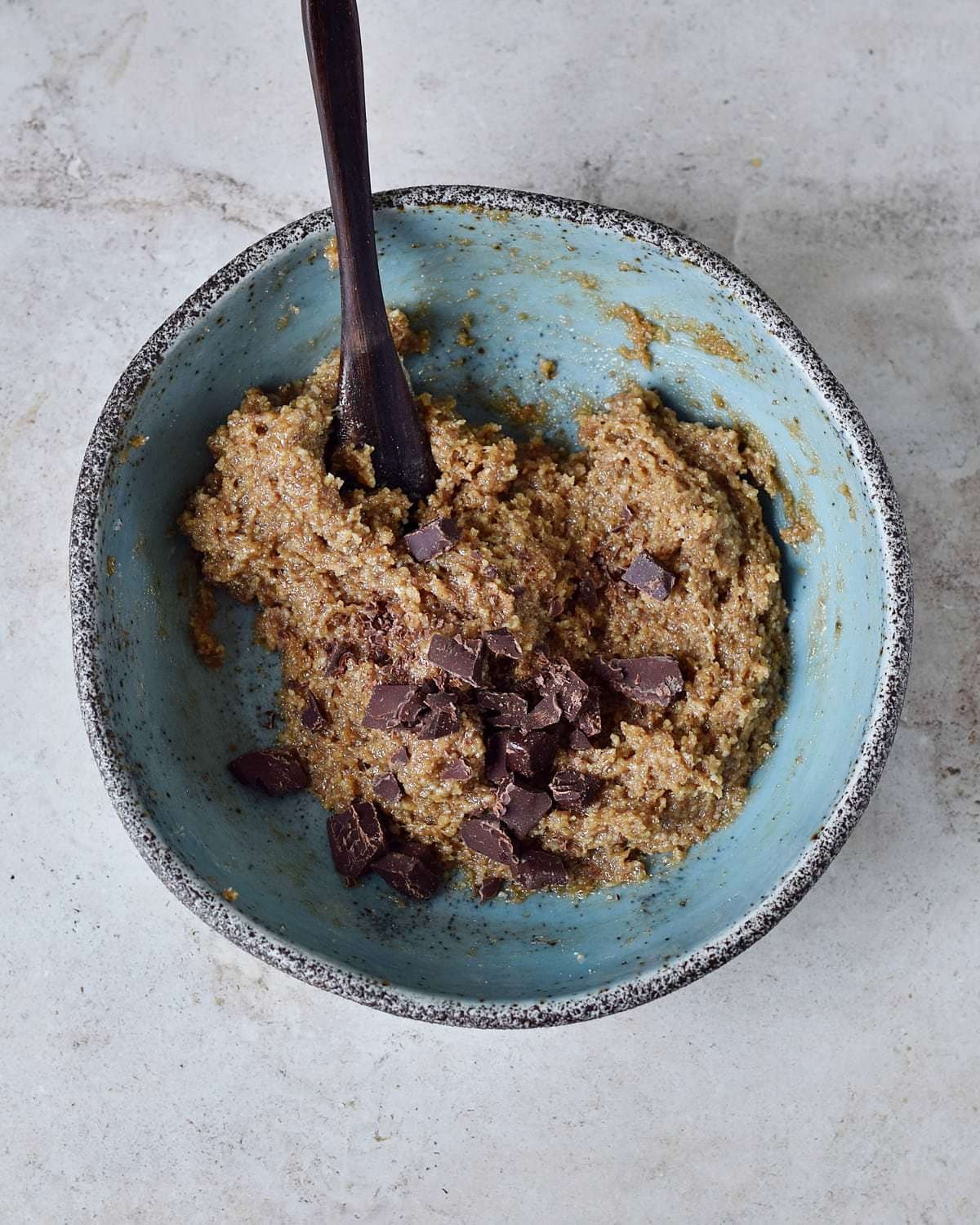 healthy vegan cookie dough in blue bowl with wooden spoon
