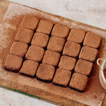 homemade condensed milk truffles with cocoa powder on wooden board