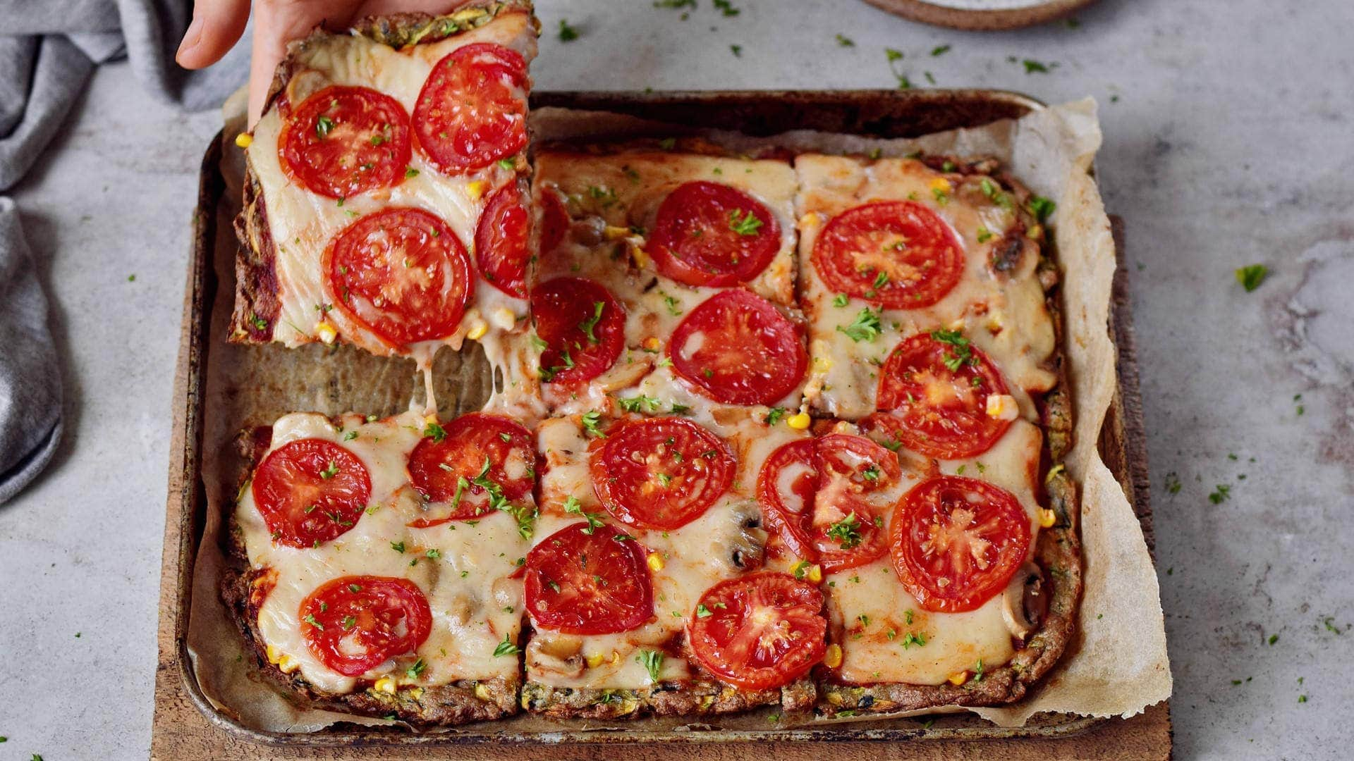 horizontal shot of keto pizza with tomatoes and vegan cheese