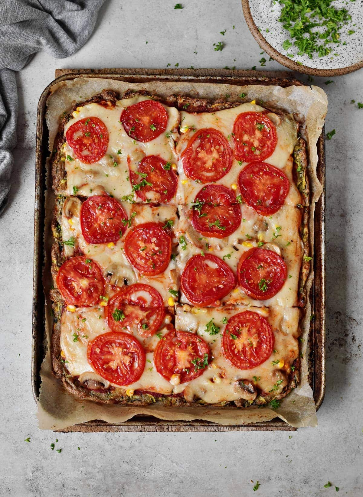 sliced rectangular gluten-free keto pizza with tomatoes and cheese