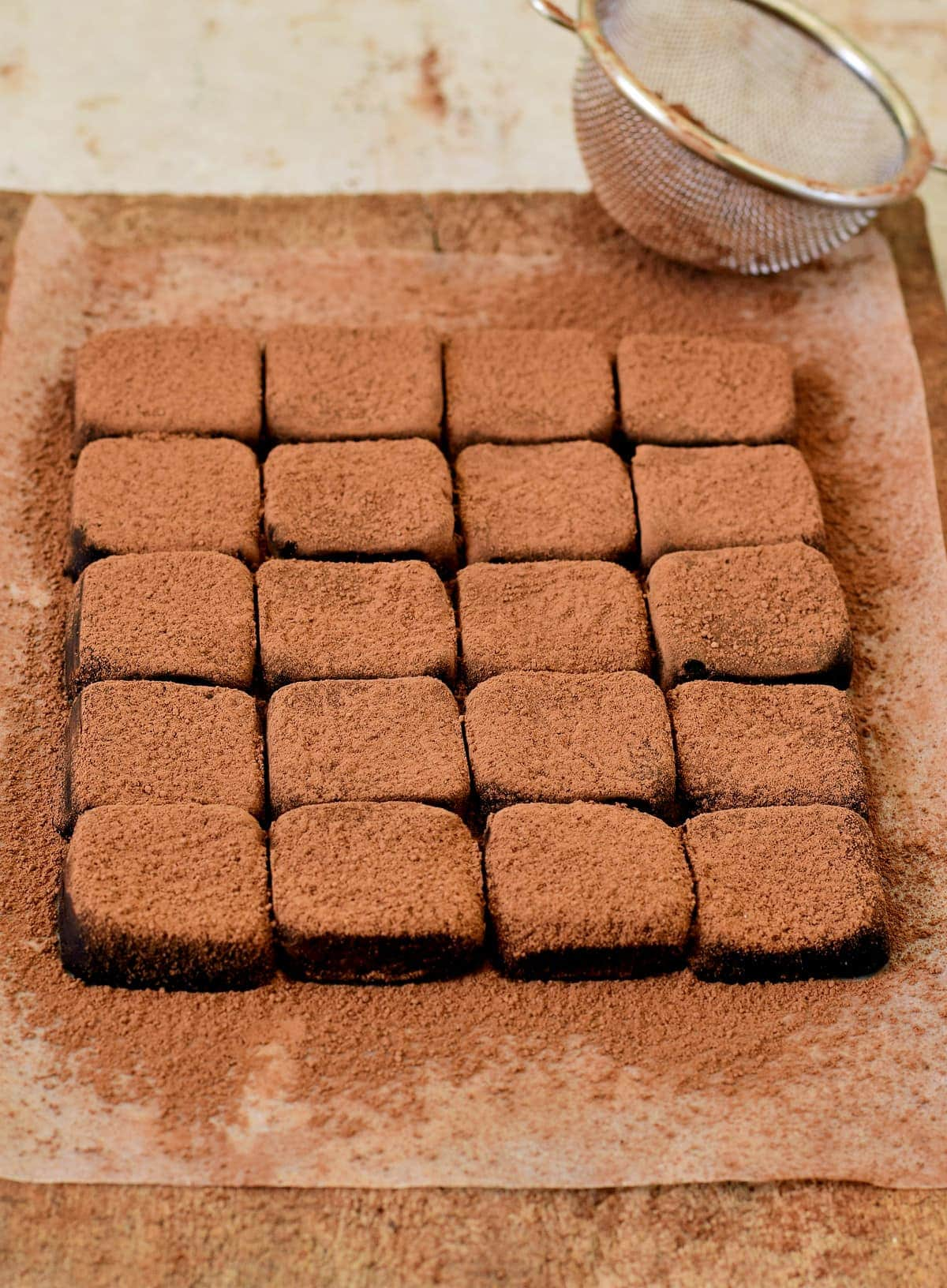 vegan chocolate fudge shaped in squares on cutting board