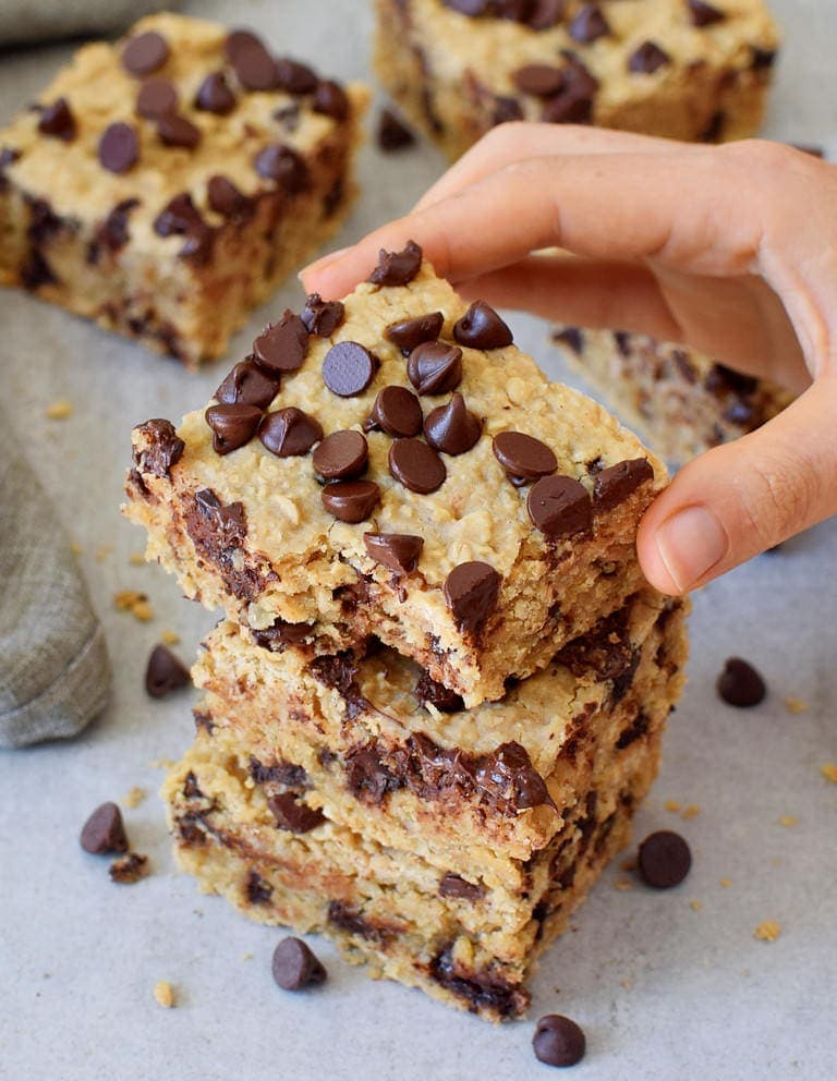 hand grabbing oat bar with chocolate