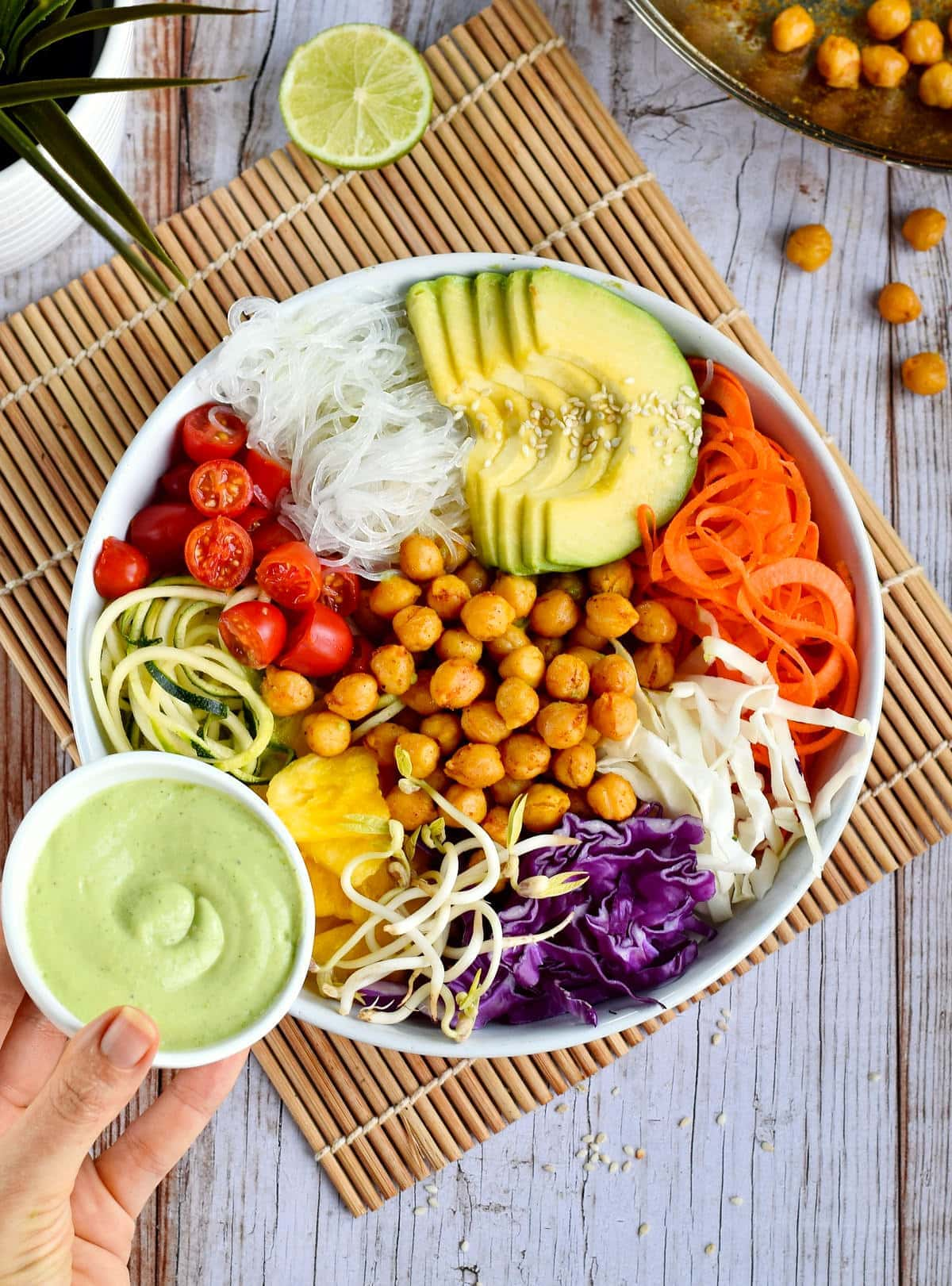 hand holding green avocado dressing next to colorful chickpea salad buddha bowl
